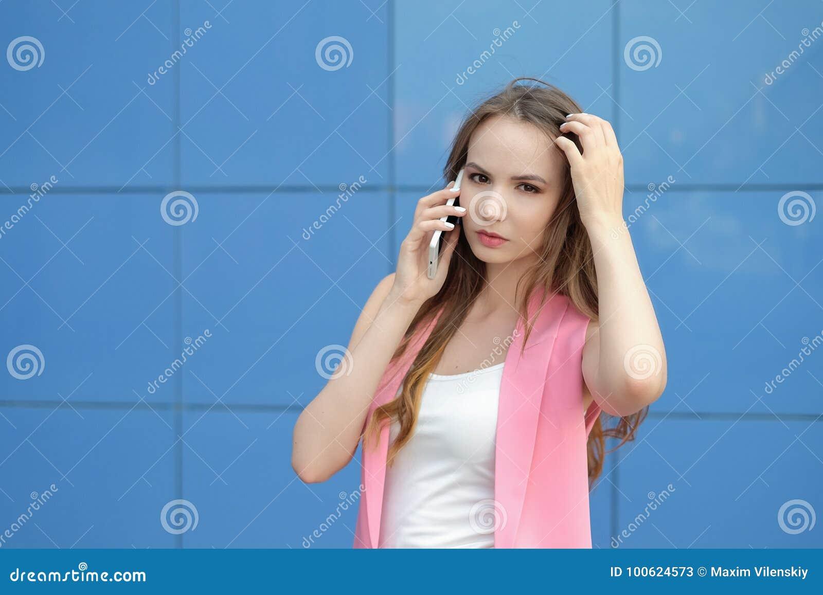Retrato del cierre hermoso sonriente de la mujer joven para arriba con el teléfono móvil al aire libre