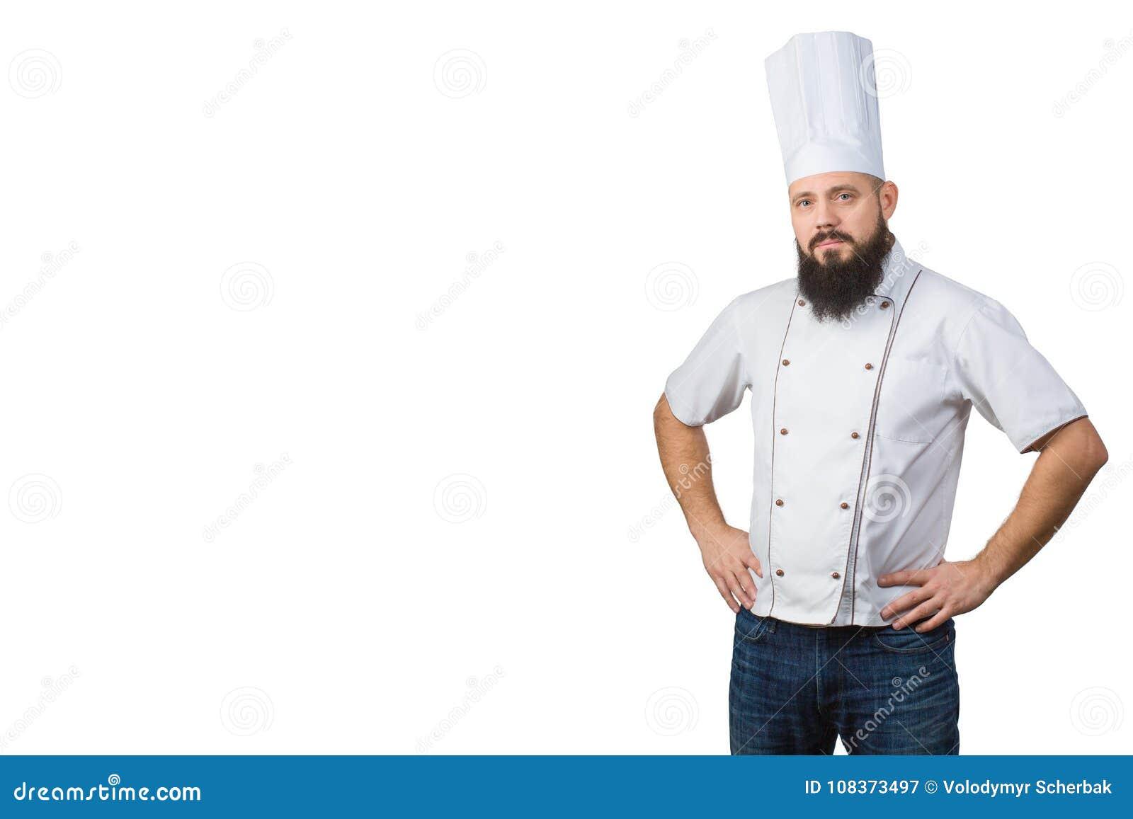 Retrato del cocinero de sexo masculino barbudo hermoso en manos uniformes en la cintura aislada en el fondo blanco, espacio de la