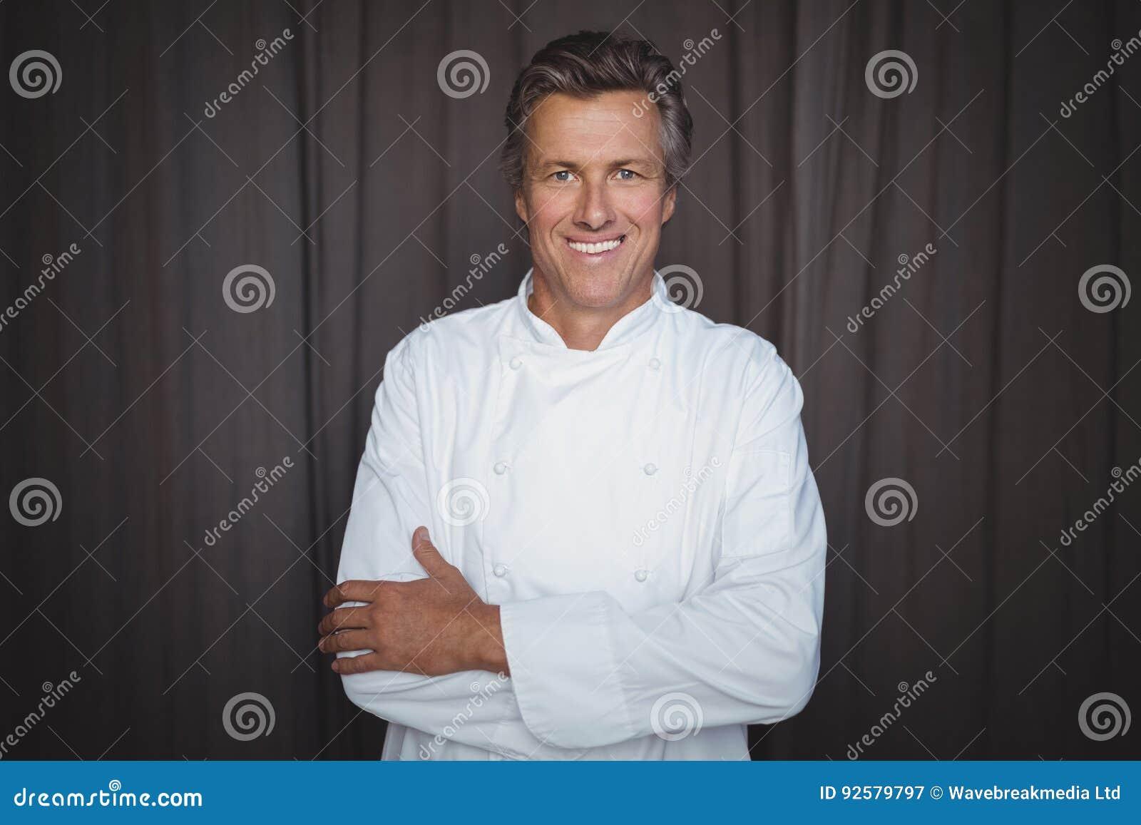 Retrato del cocinero hermoso que se coloca con los brazos cruzados