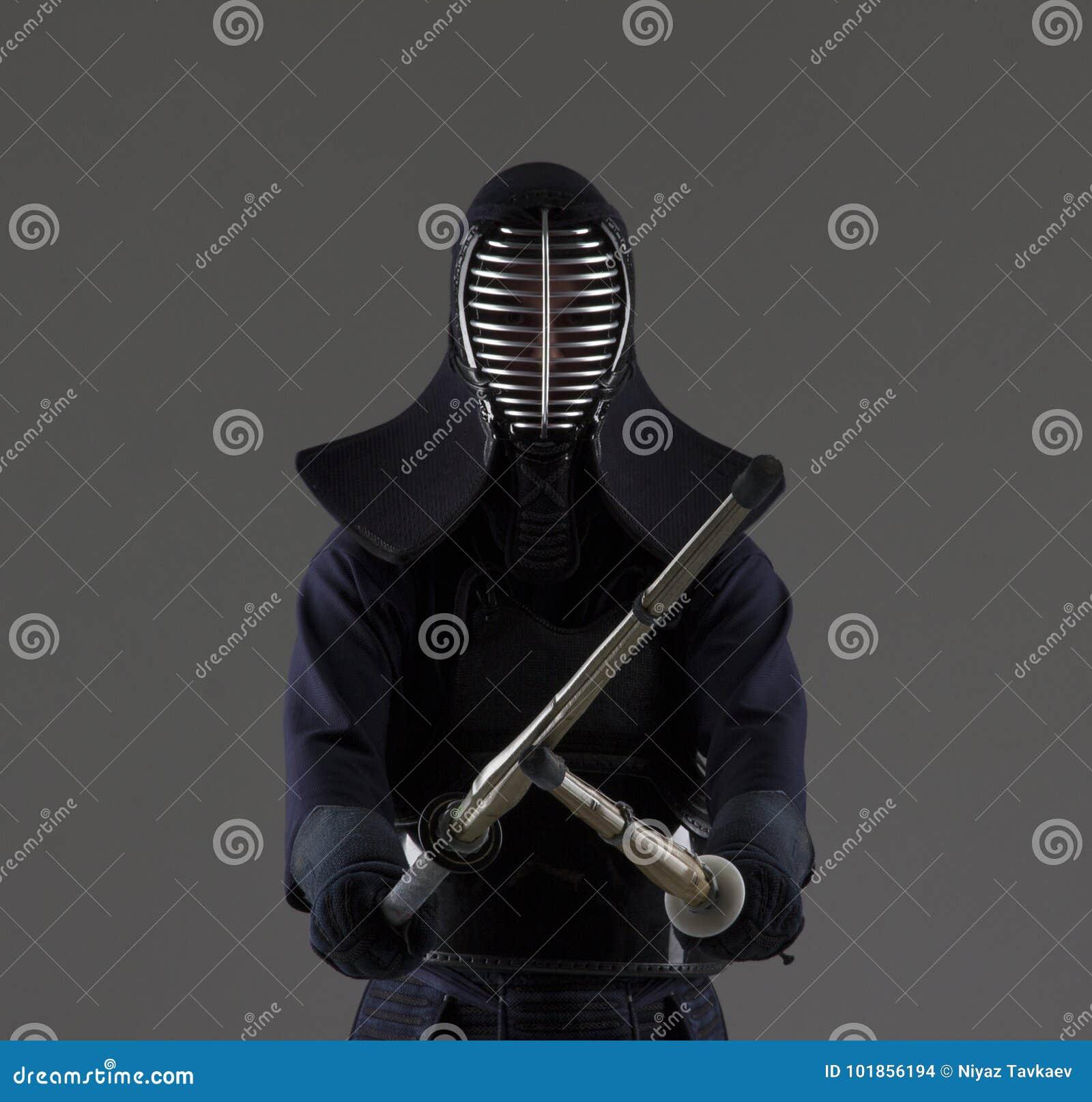 Retrato del combatiente del kendo del hombre con dos espadas de bambú en uniforme tradicional