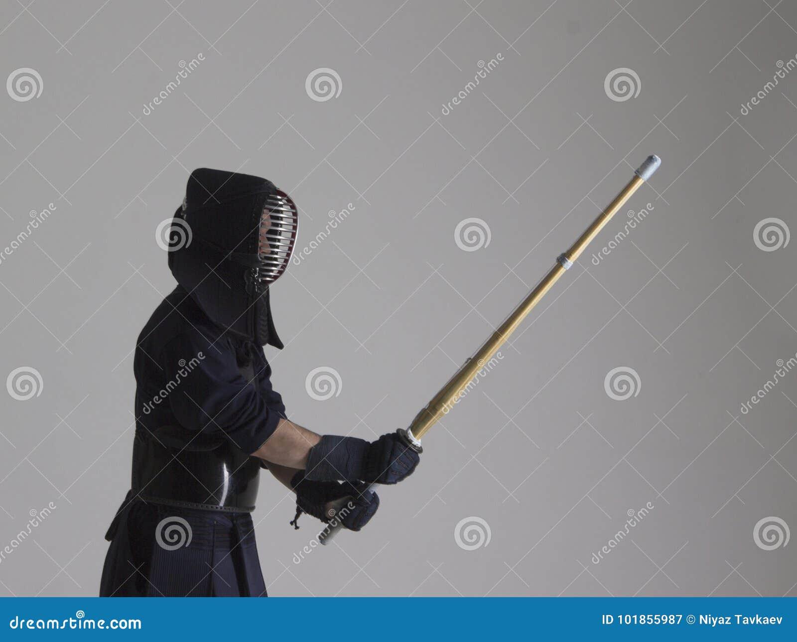 Retrato del combatiente del kendo del hombre con shinai Tiro del estudio