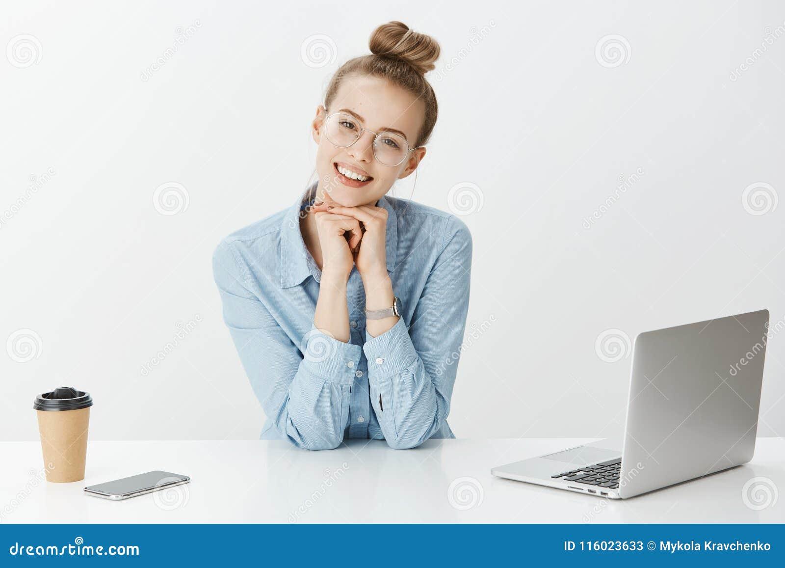 Retrato del compañero de trabajo femenino europeo feliz enfocado en vidrios, cabeza que se inclina en las manos y la mirada con s