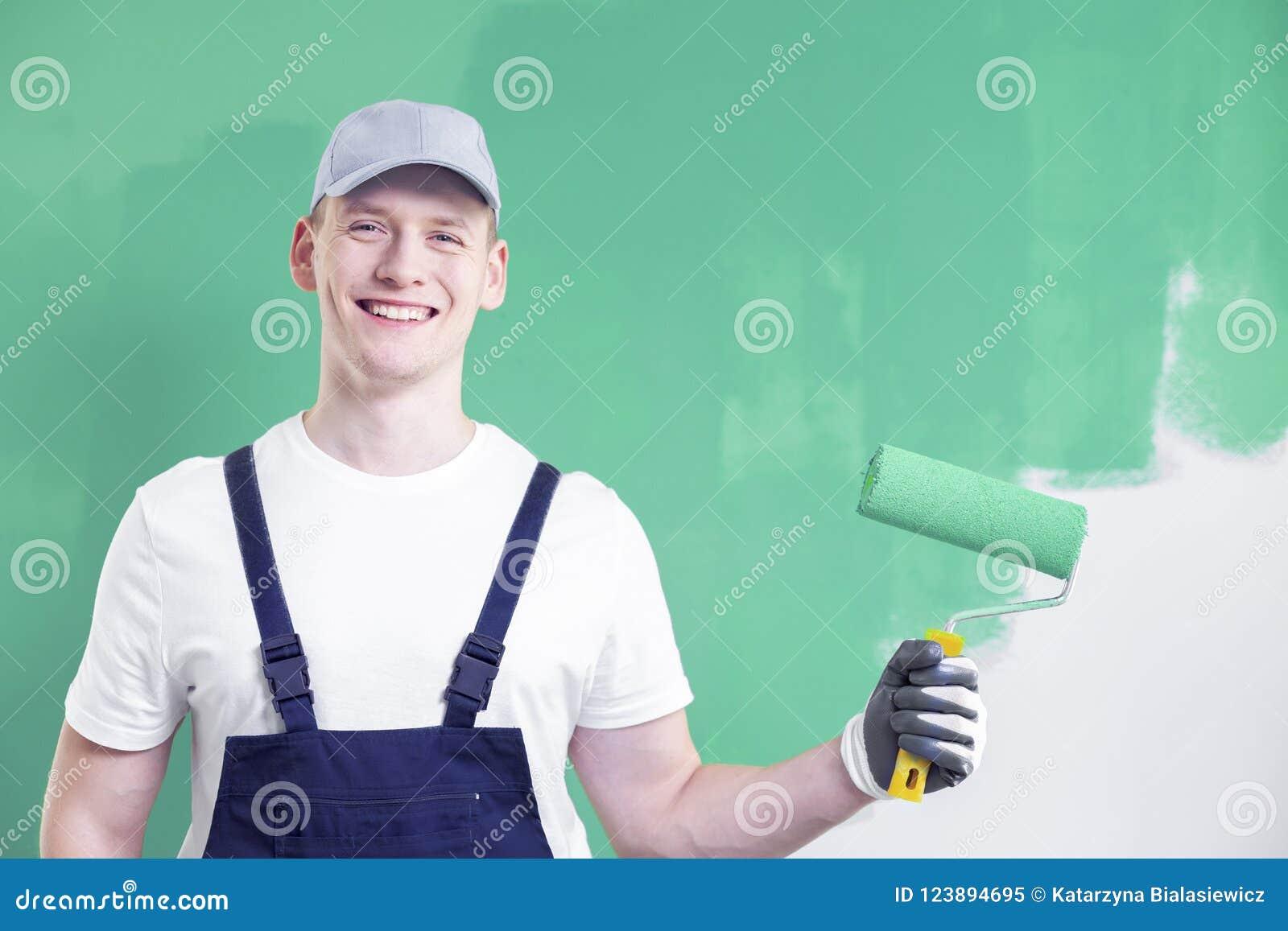Retrato del cuerpo superior de un trabajador casero joven, sonriente p de la renovación