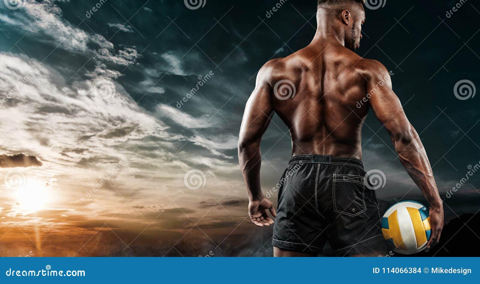 Retrato del deportista afroamericano, jugador de voleibol de playa con una bola sobre fondo del cielo Hombre joven apto adentro
