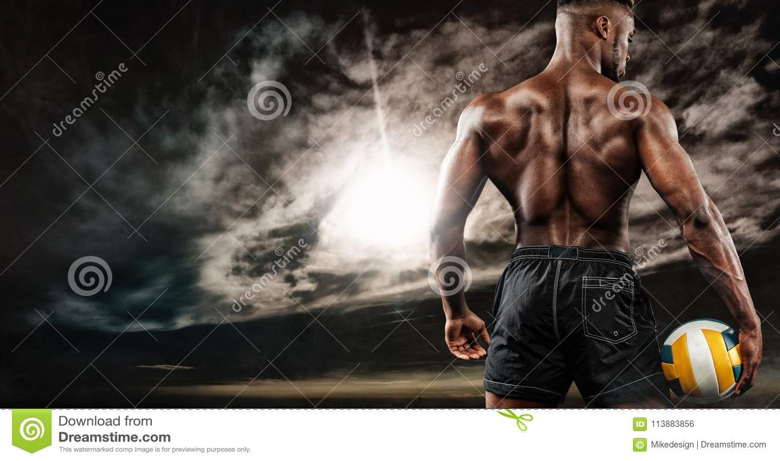 Retrato del deportista afroamericano, jugador de voleibol de playa con una bola sobre puesta del sol Hombre joven apto en ropa de
