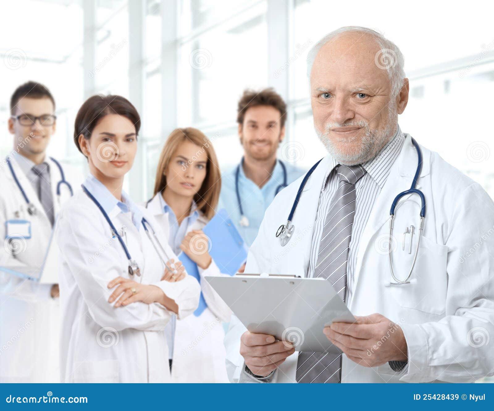 Retrato del doctor envejecido con los residentes médicos
