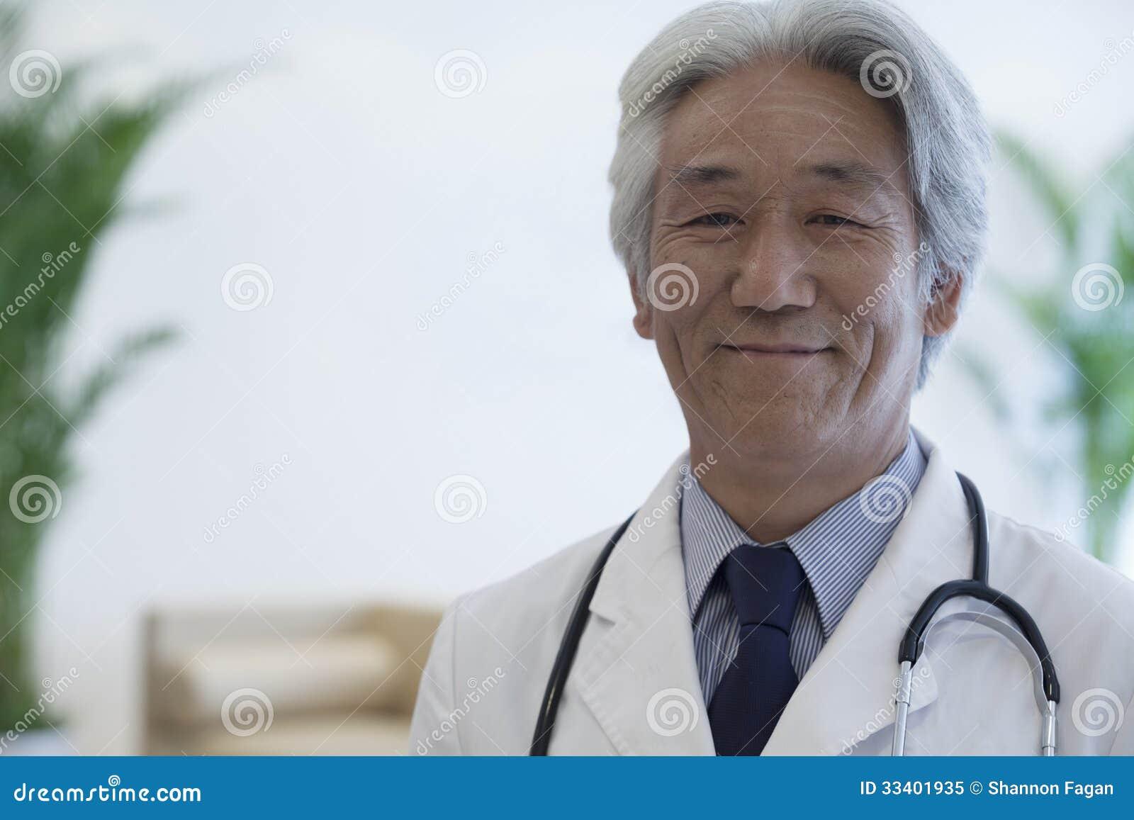 Retrato del doctor maduro que mira la cámara y la sonrisa