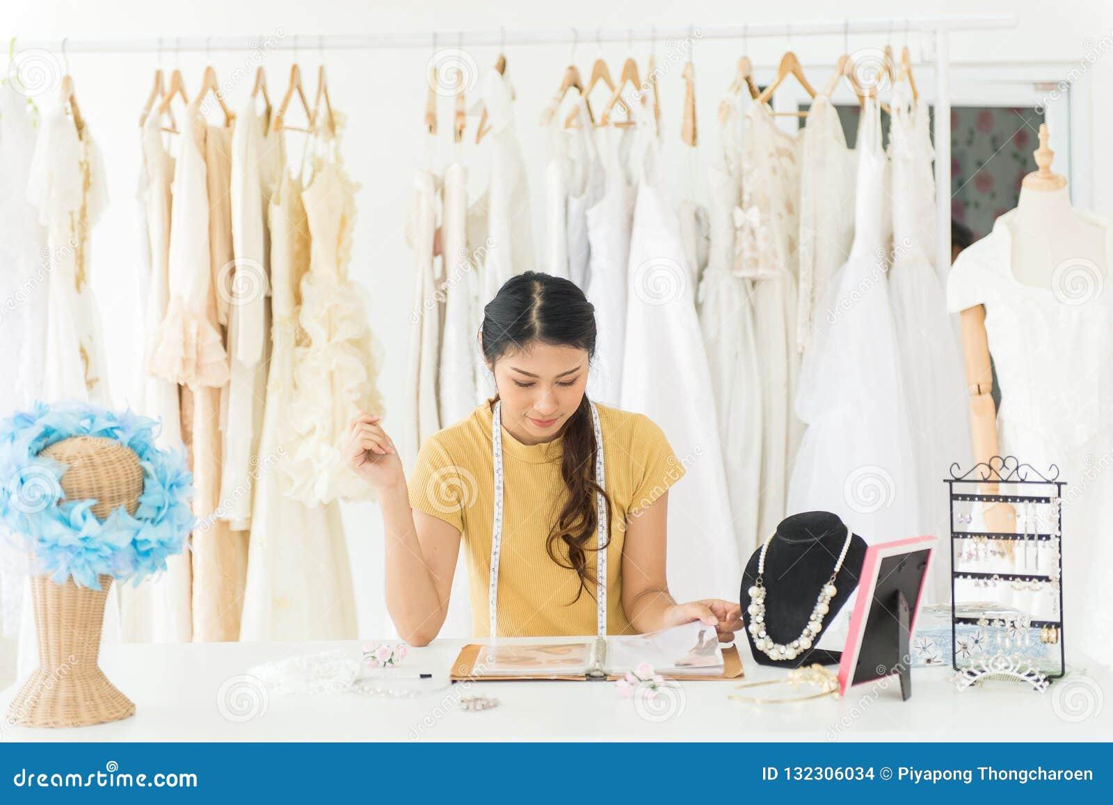 Retrato del dueño de tienda asiático del vestido de boda de la mujer, de la modista de sexo femenino hermosa en tienda y de la pe