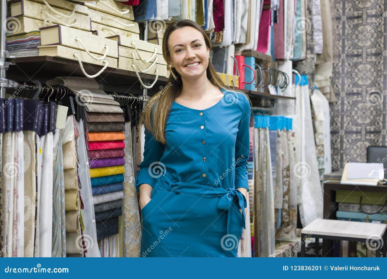 Retrato del dueño maduro feliz de la mujer en la tienda interior de las telas, muestras de la tela del fondo Tienda de la materia