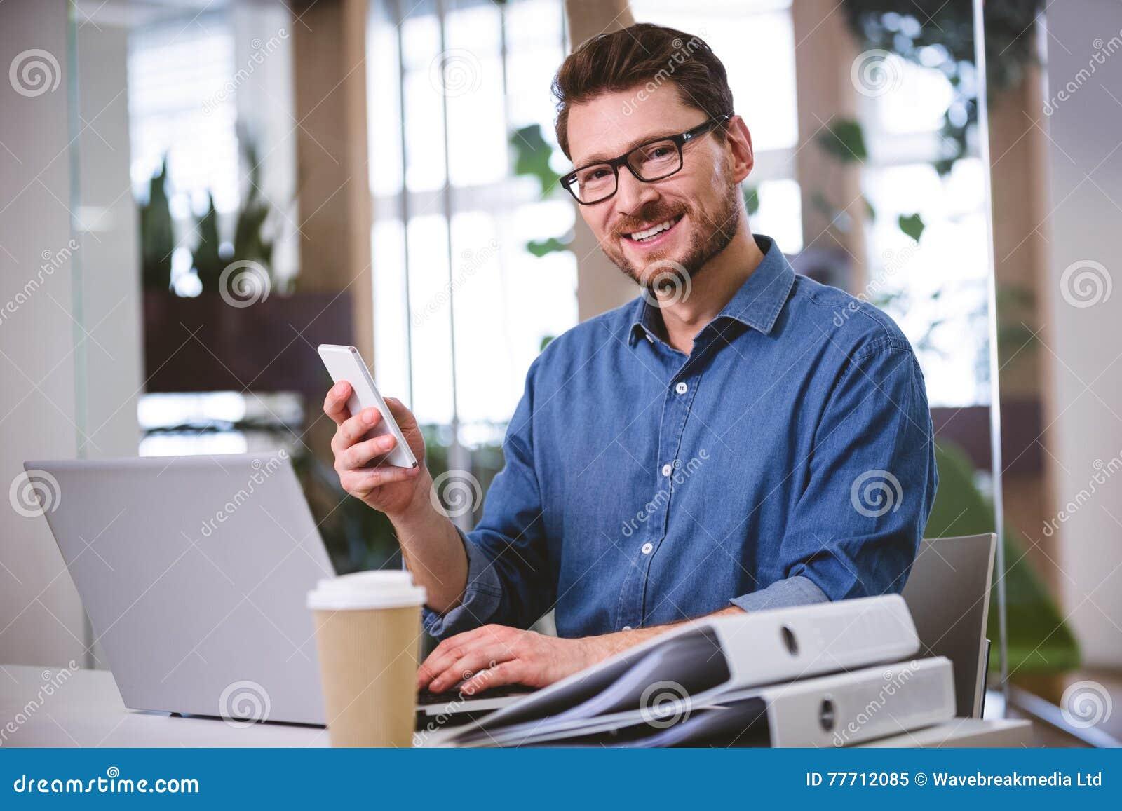 Retrato del ejecutivo confiado que usa el teléfono móvil en la oficina creativa