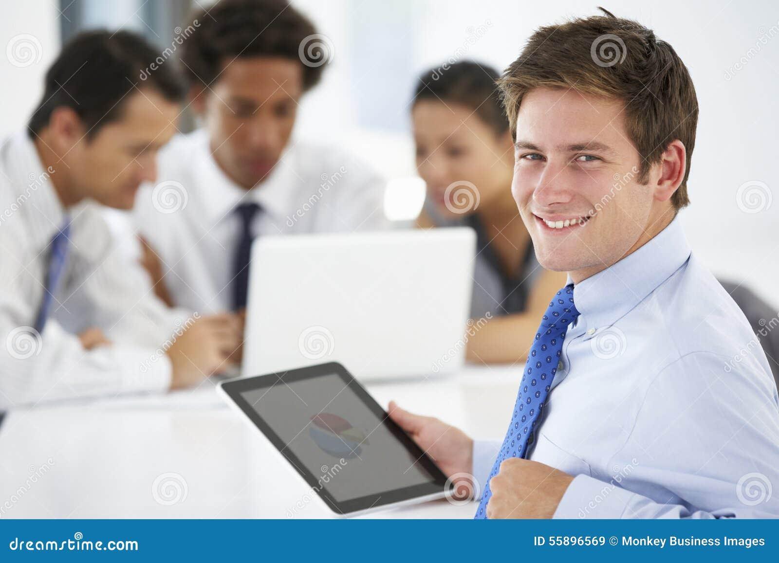 Retrato del ejecutivo de sexo masculino que usa la tableta con la oficina Mee