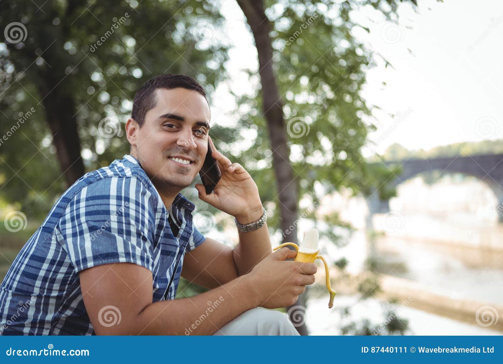 Retrato del ejecutivo que habla en el teléfono móvil mientras que comiendo el plátano