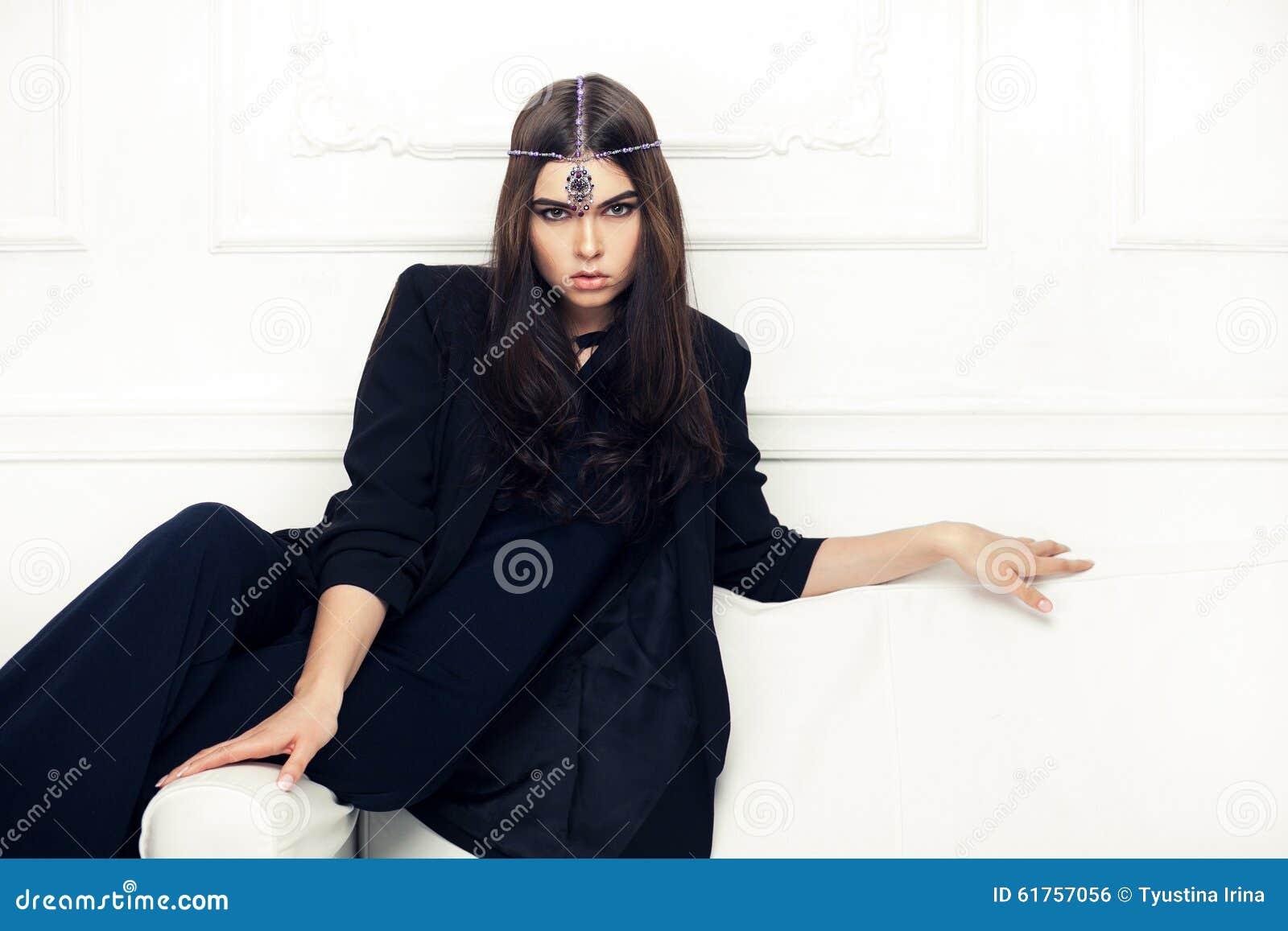 Retrato del estilo de Vogue de la mujer morena hermosa en un sofá con