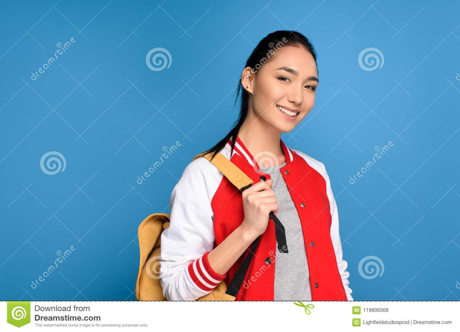 Retrato del estudiante asiático sonriente con la mochila