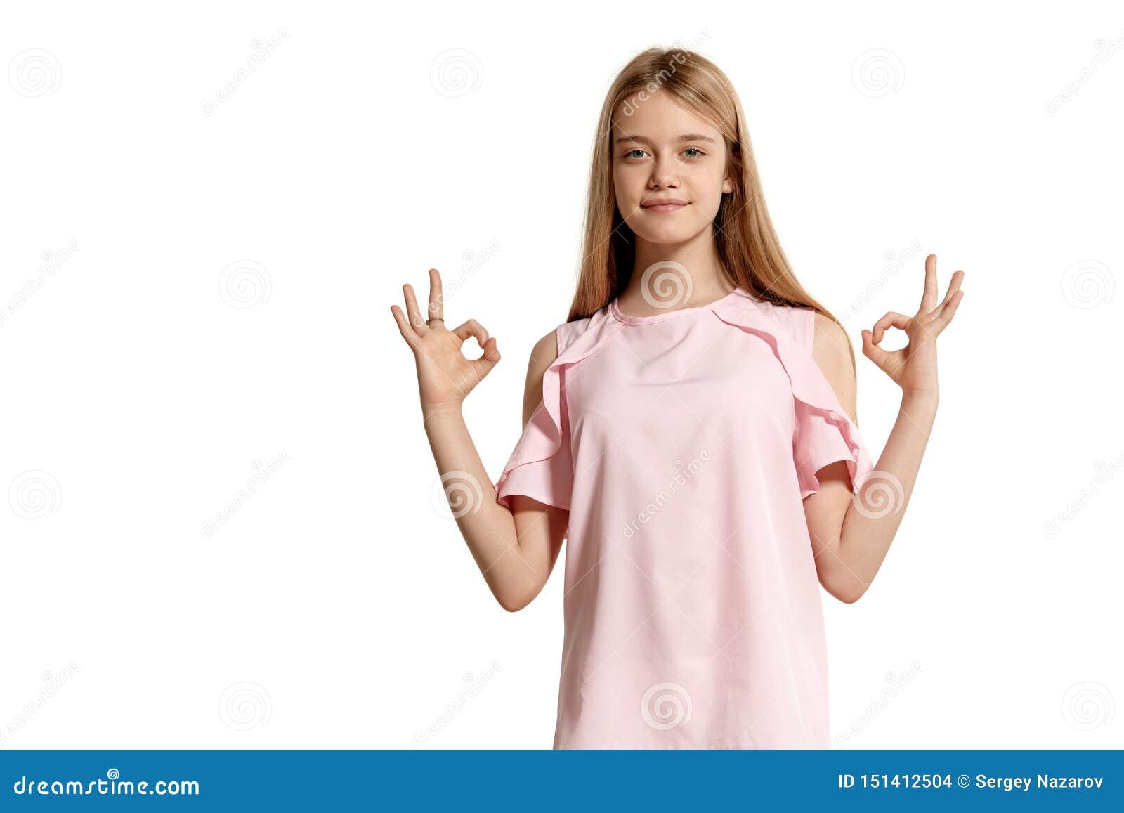 Retrato del estudio de un adolescente rubio de la muchacha hermosa en una presentación rosada de la camiseta aislado en el fondo