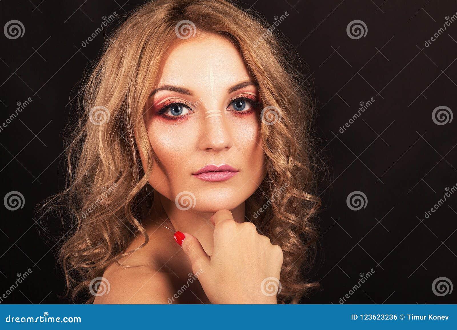 Retrato del estudio Muchacha hermosa con maquillaje de la tarde en un fondo negro