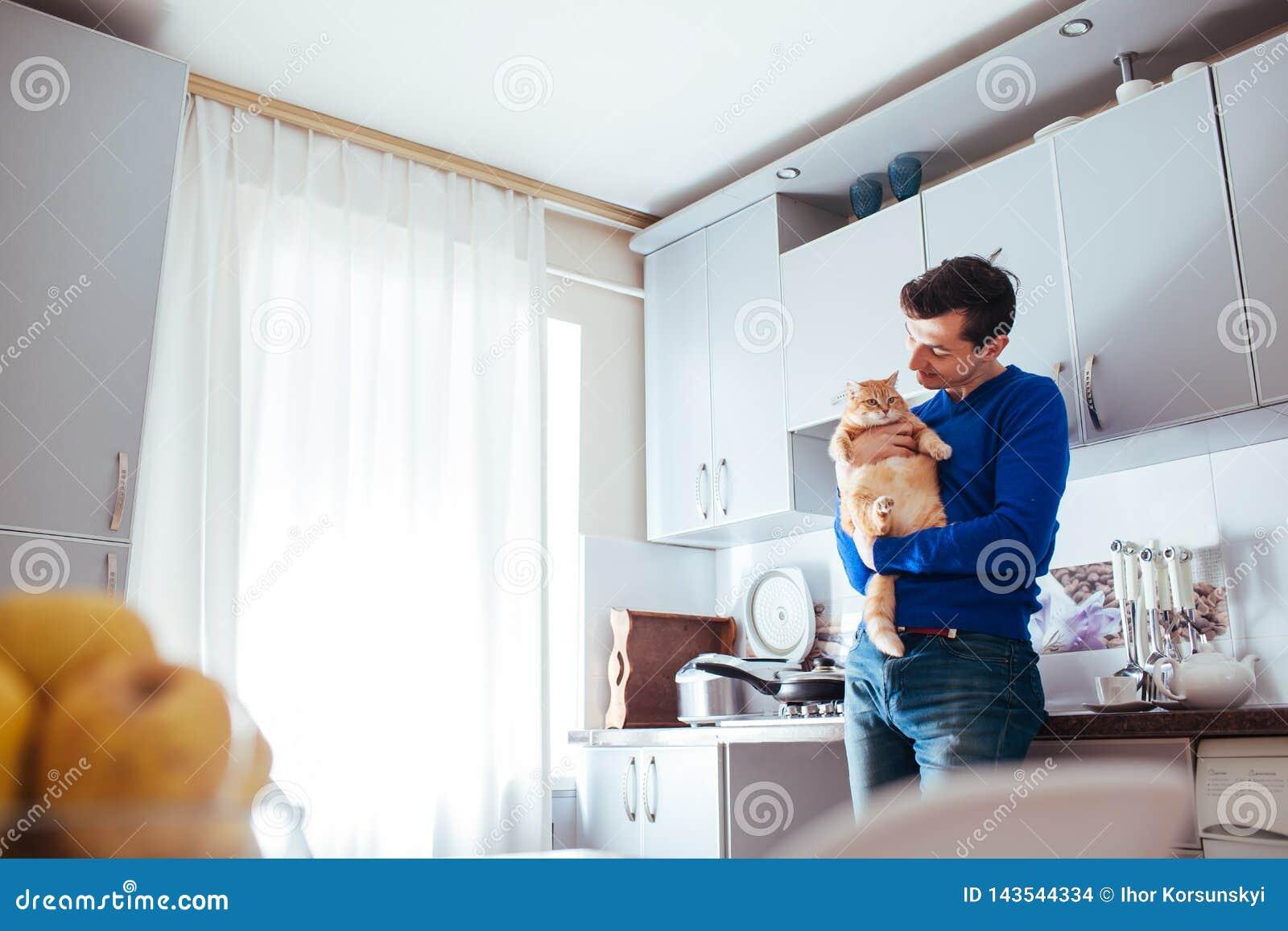 Retrato del gato hermoso de la tenencia del hombre joven en la cocina