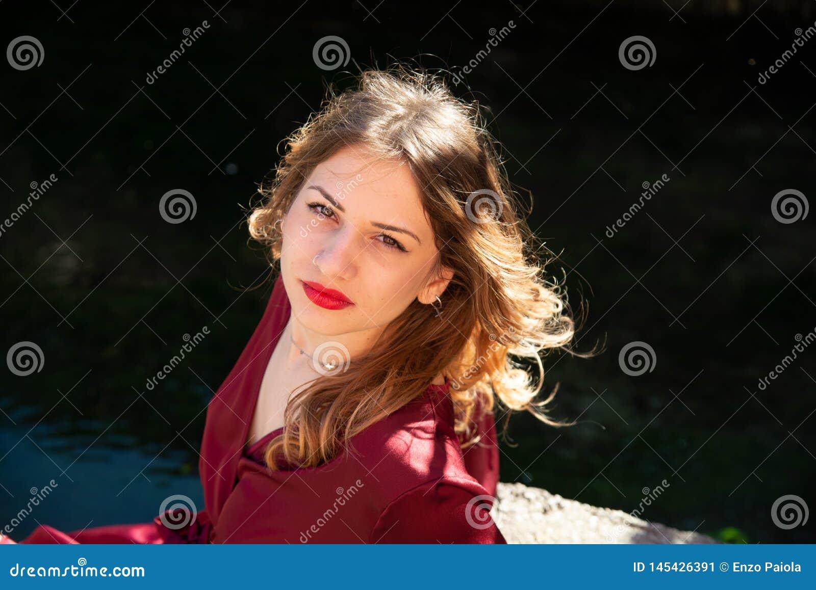 Retrato del Headshot de una muchacha rubia en la extensi?n ligera natural a lo largo del banco de un r