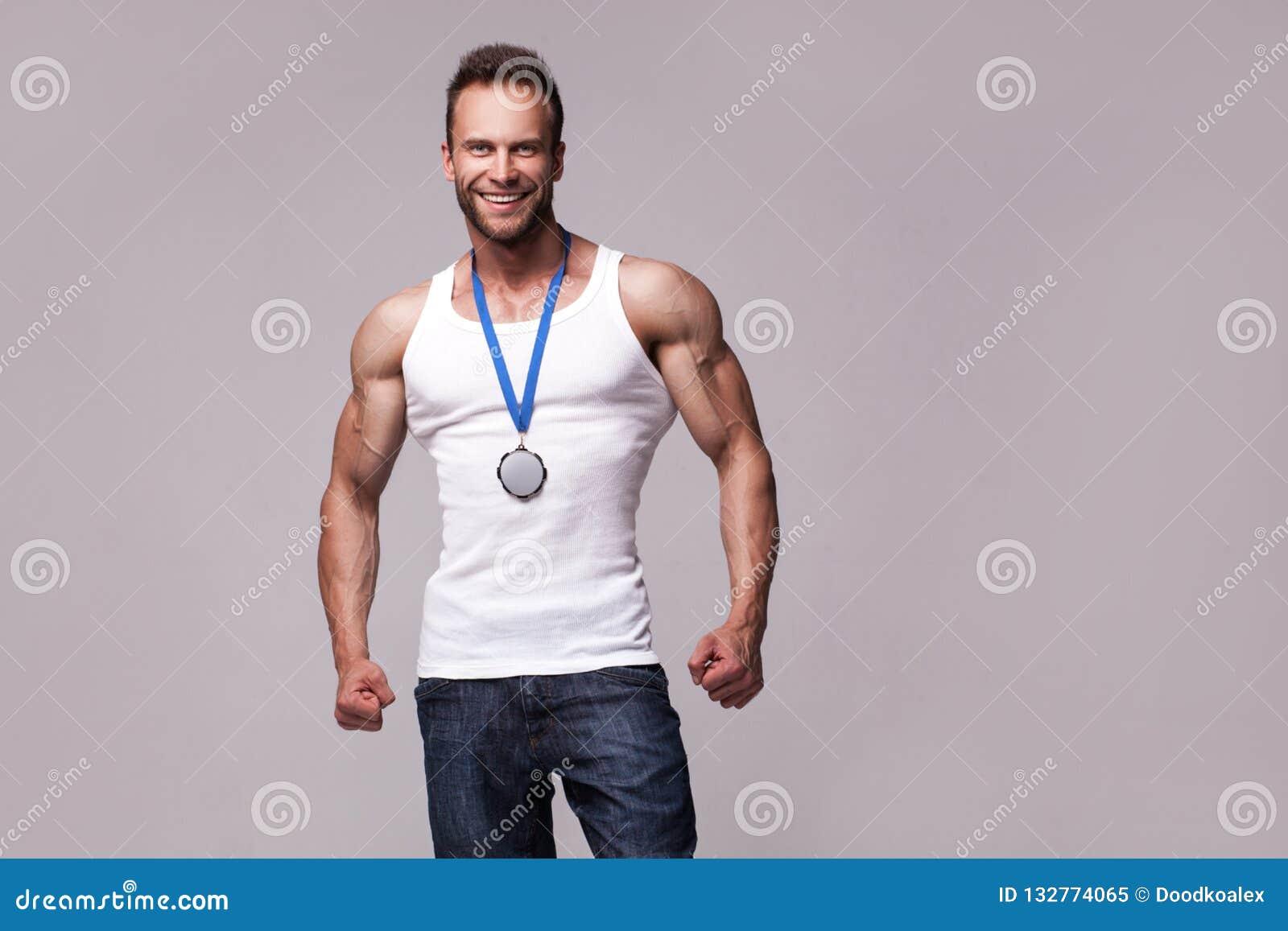 Retrato del hombre atlético en la camiseta blanca con la medalla de los campeones