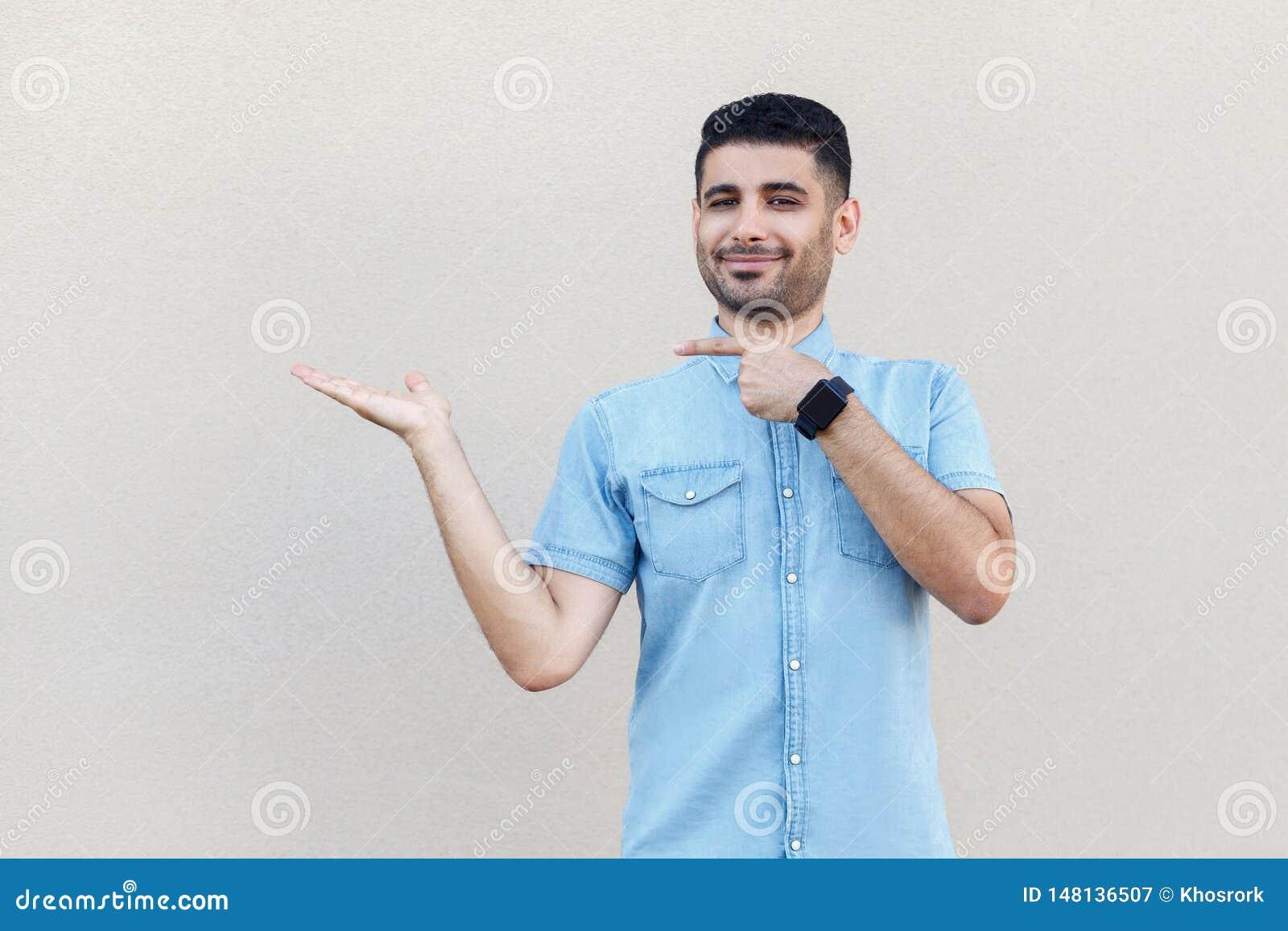 Retrato del hombre barbudo joven hermoso satisfecho feliz en la camisa azul que se coloca, sosteniéndose, señalando algo y mirand