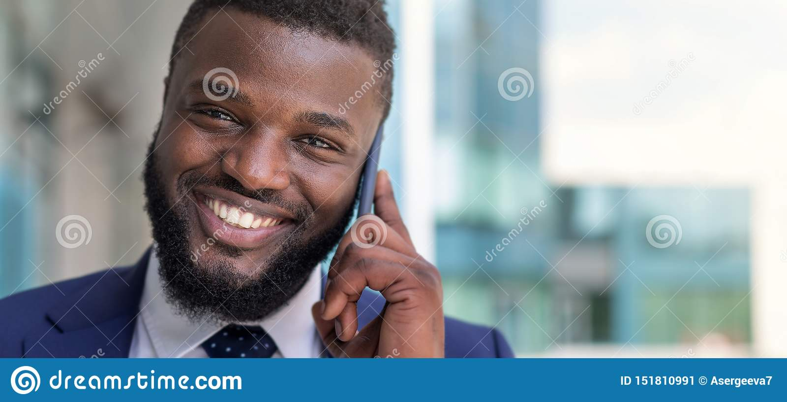 Retrato del hombre de negocios afroamericano sonriente que habla por el teléfono al aire libre Copie el espacio