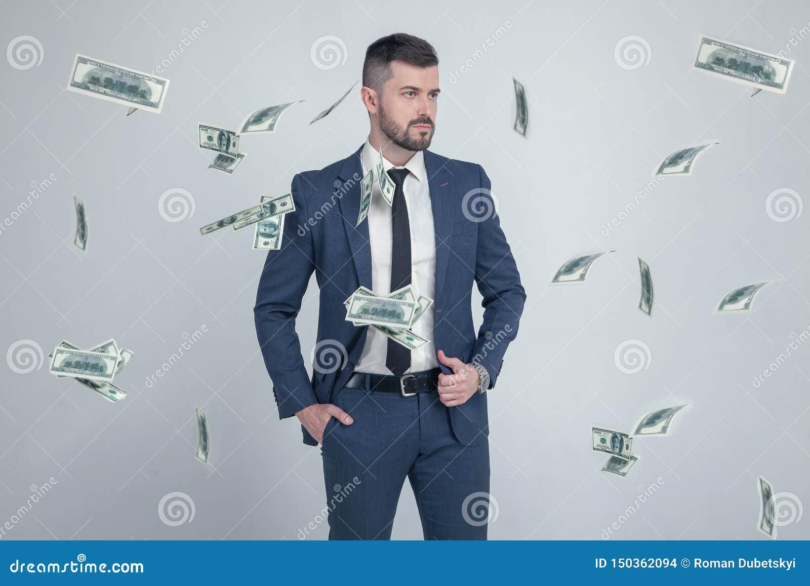 Retrato del hombre de negocios elegante con los billetes de banco de la caída del dólar en fondo gris vestido en un traje con un