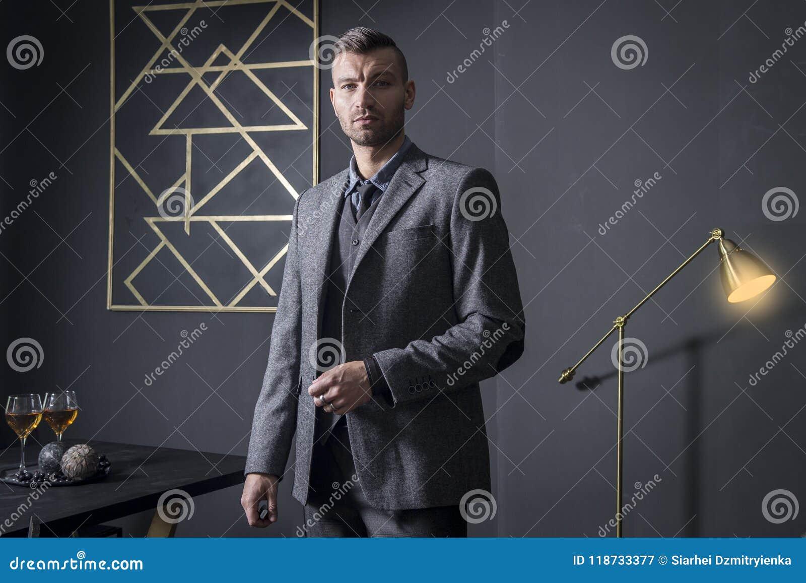 Retrato del hombre de negocios hermoso elegante en el apartamento de lujo Hombre de negocios en interior oscuro hombre en negocio