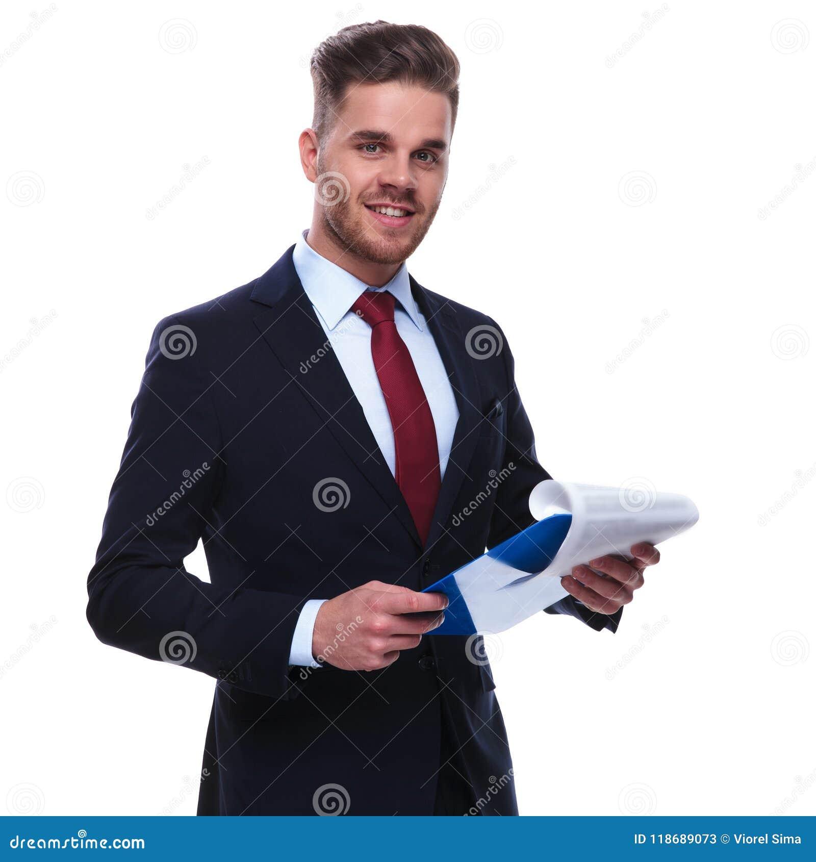 Retrato del hombre de negocios joven que comprueba sus ficheros y sonrisa