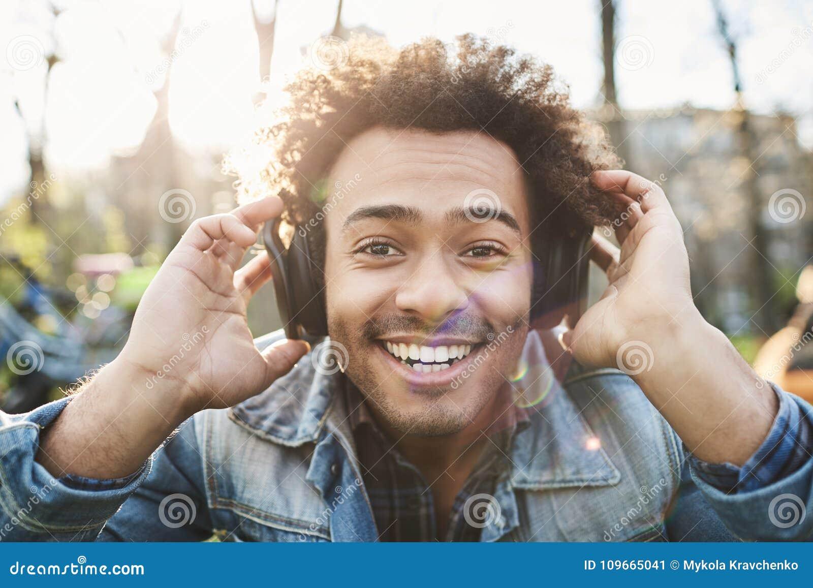 Retrato del hombre de piel morena adulto positivo que sonríe ampliamente mientras que se sienta en parque, escuchando la música e