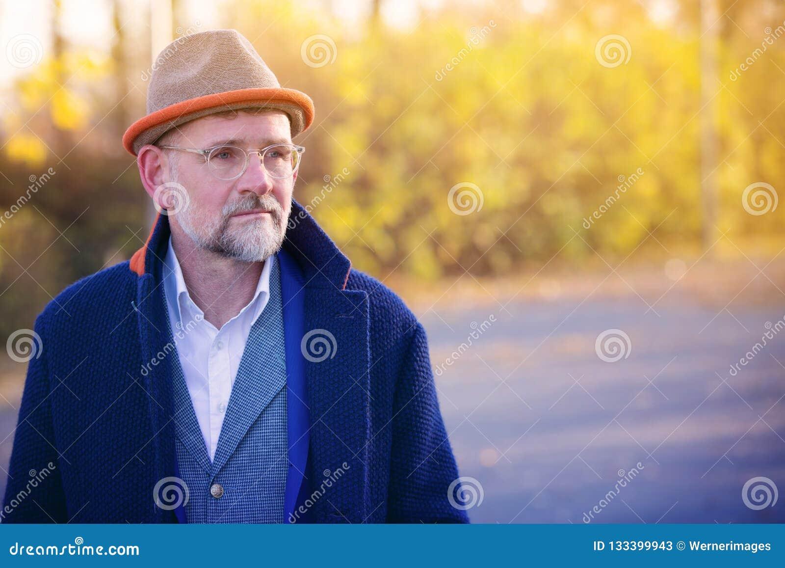 Retrato del hombre en su 50s en aire libre azul del traje y de la capa