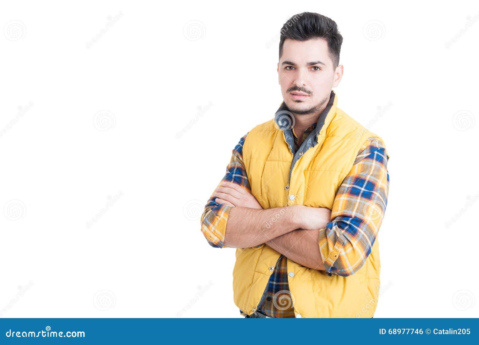Retrato del hombre hermoso que se coloca con los brazos cruzados