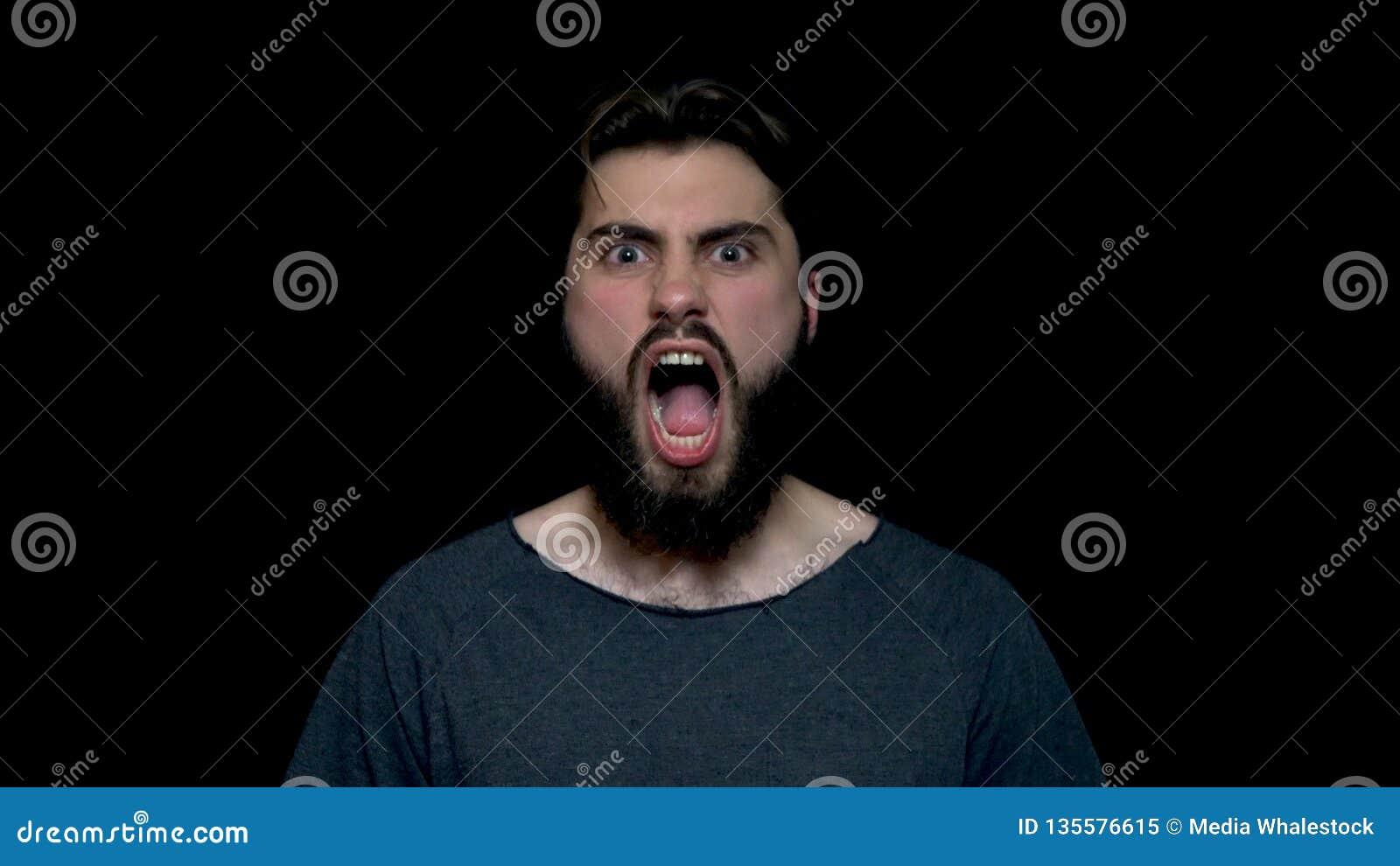 Retrato del hombre hermoso del rugido con la barba que se coloca y que grita con la boca abierta grande, aislado en fondo negro J