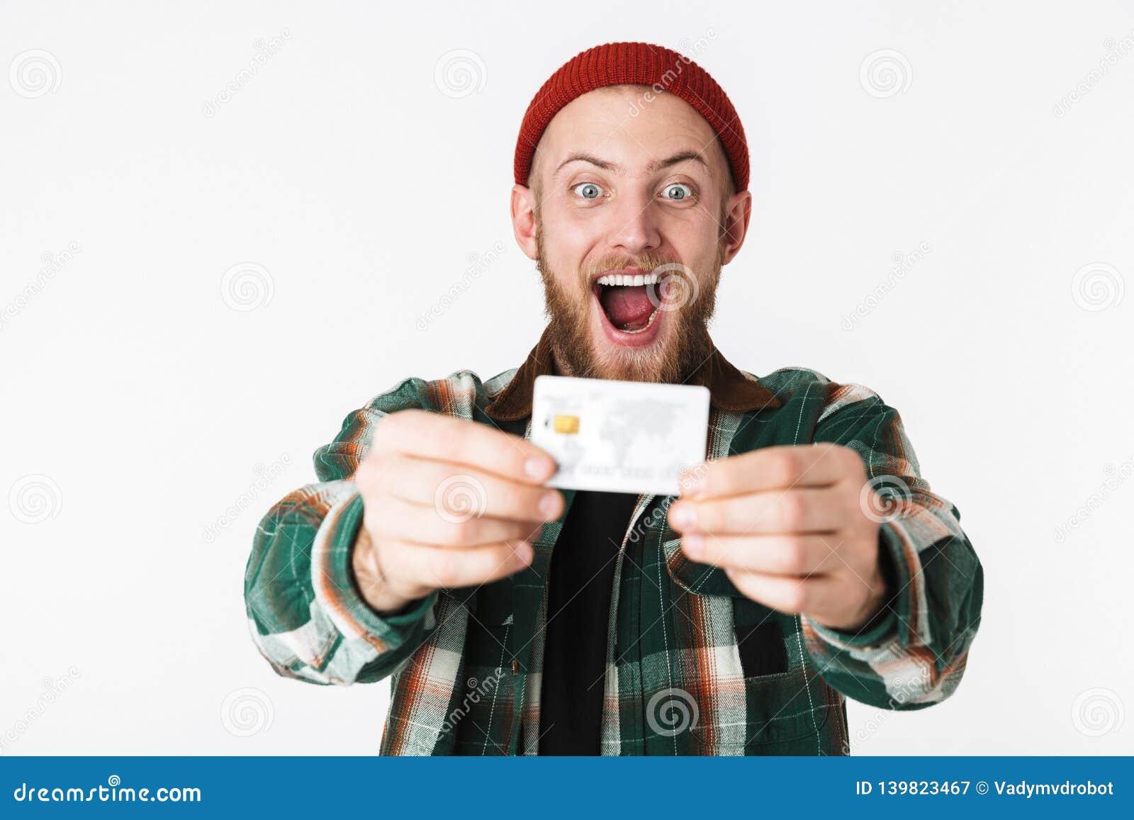 Retrato del hombre del inconformista que ríe y que sostiene la tarjeta de crédito, mientras que se coloca aislado sobre el fondo