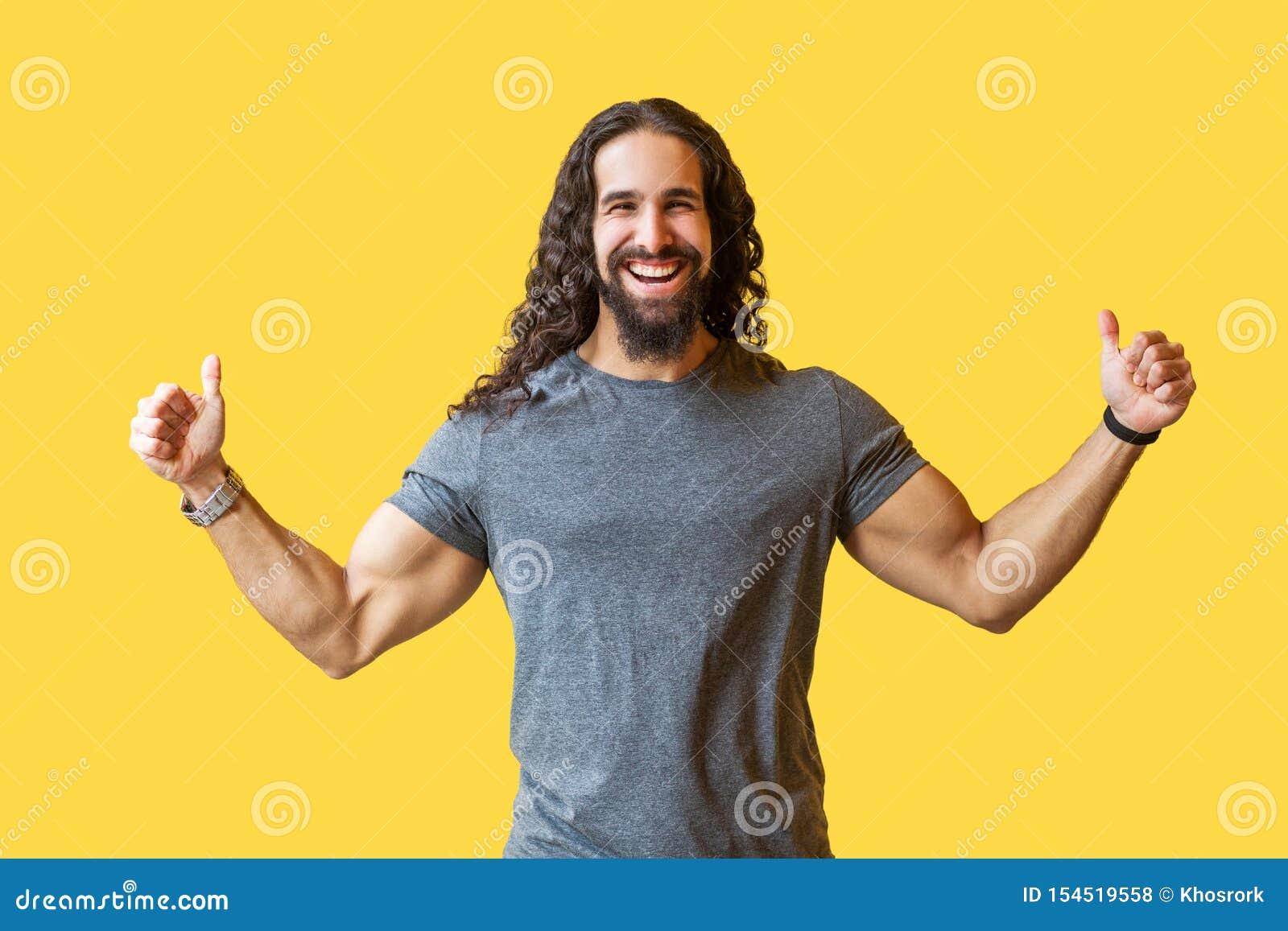 Retrato del hombre joven barbudo feliz con el pelo rizado largo en la situación gris de la camiseta con los pulgares para arriba