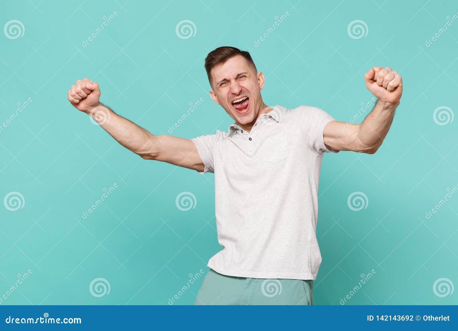 Retrato del hombre joven de griterío extático en puños de apretón de la ropa casual como el ganador aislado en la turquesa azul