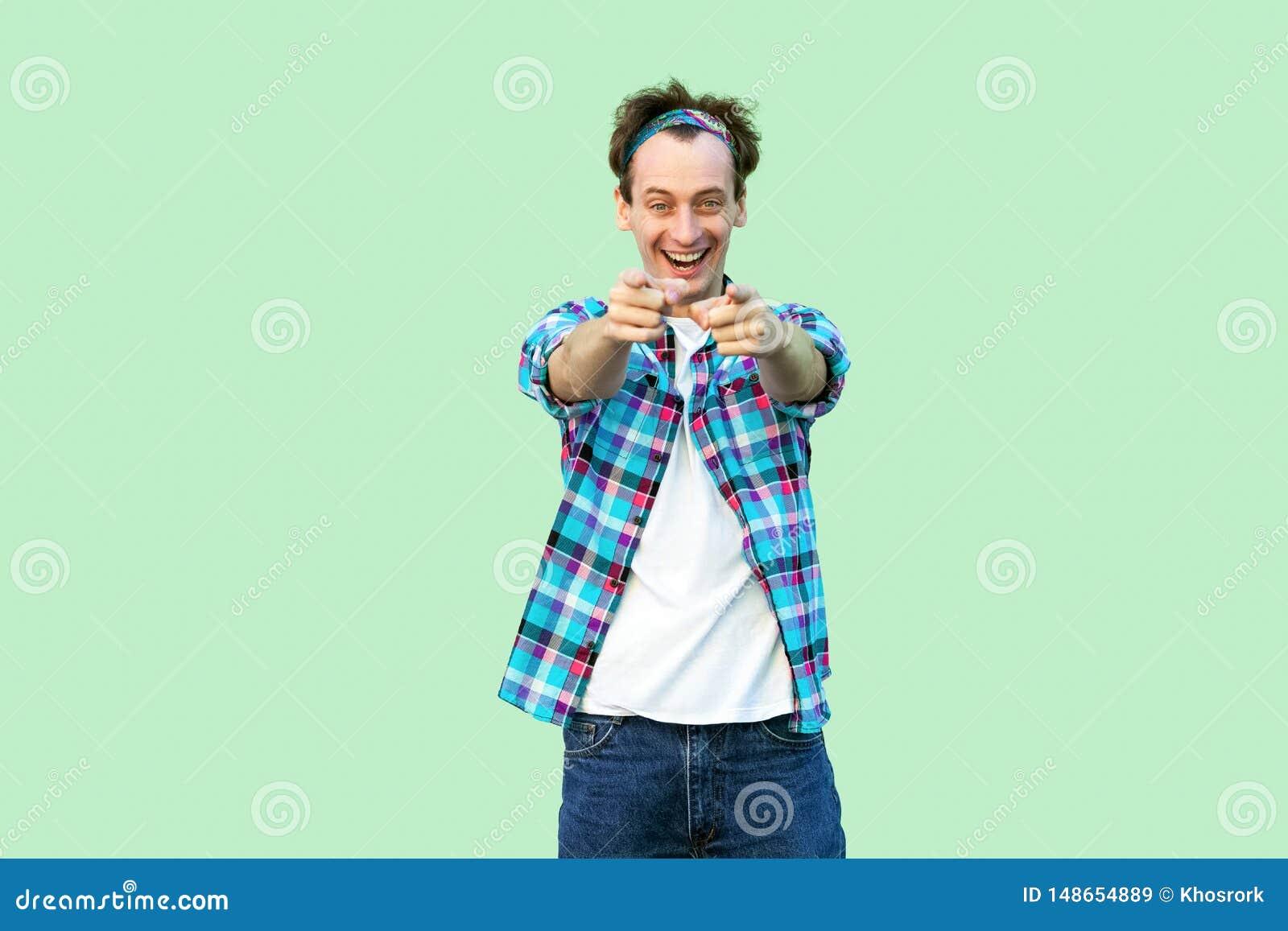 Retrato del hombre joven emocionado en la situación a cuadros azul casual de la camisa y de la venda con sonrisa dentuda, mirando