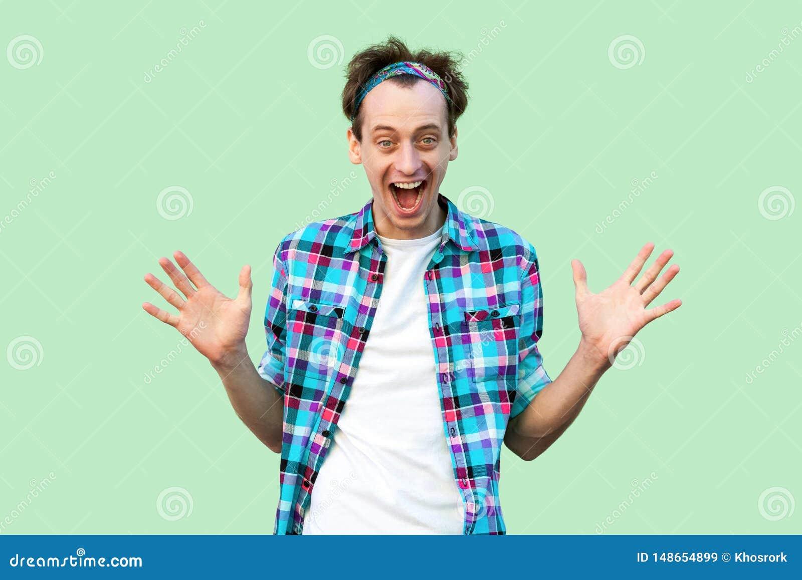Retrato del hombre joven feliz sorprendido en la situaci?n a cuadros azul casual de la camisa y de la venda, de brazos aumentados