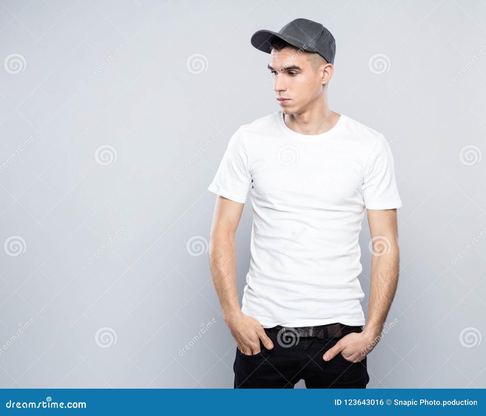 Retrato del hombre joven fresco en gorra de béisbol y la camiseta blanca