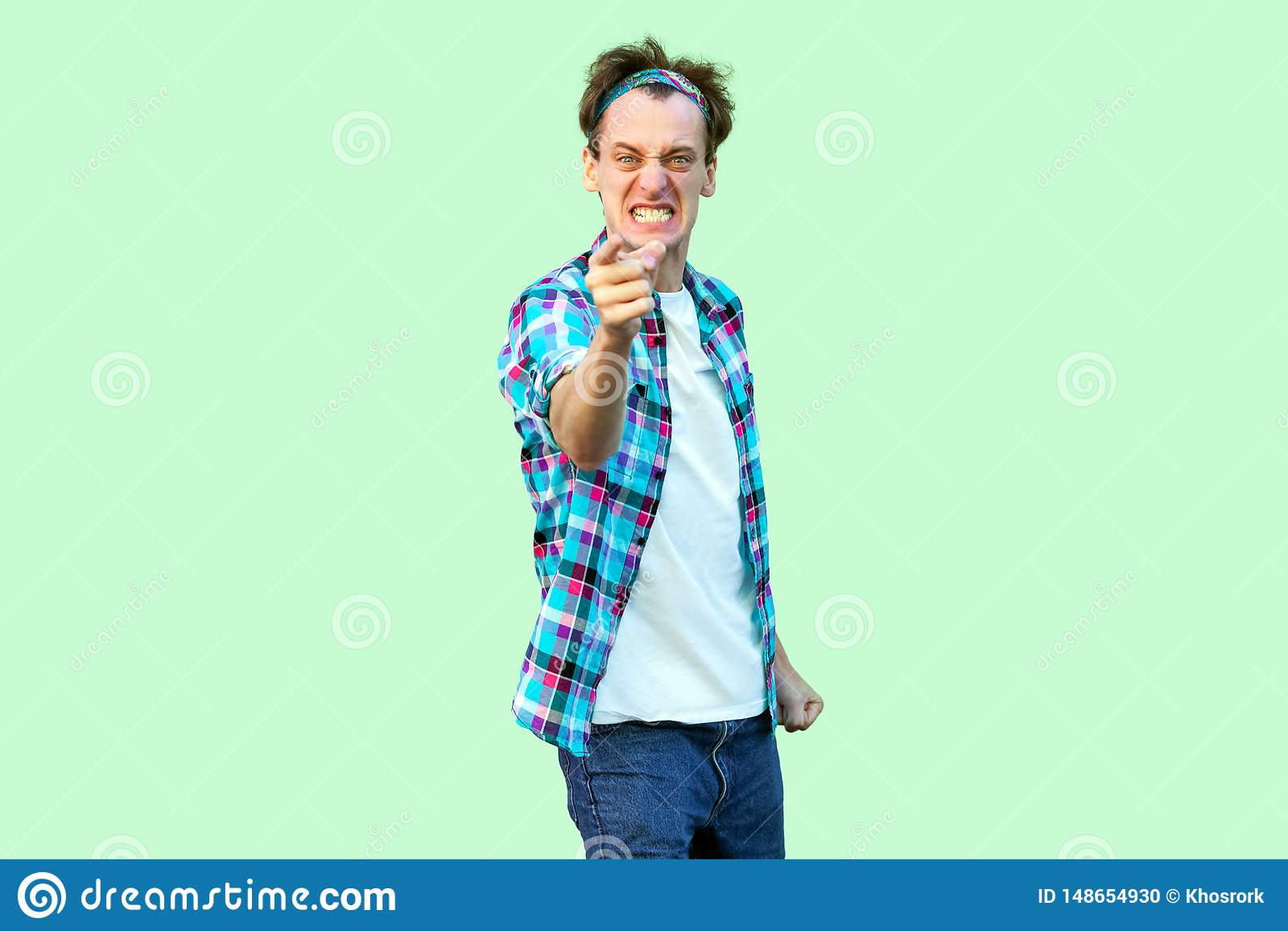 Retrato del hombre joven nervioso enojado en la situaci?n a cuadros azul casual de la camisa y de la venda, apretando los dientes