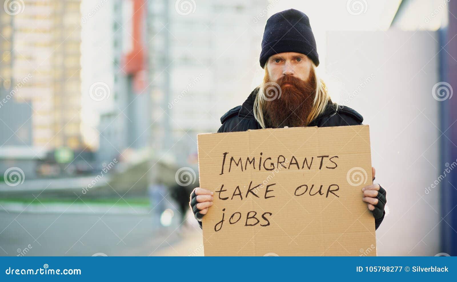 Retrato del hombre sin hogar joven con la cartulina que mira la cámara y muy trastornado debido a crisis de los inmigrantes en Eu