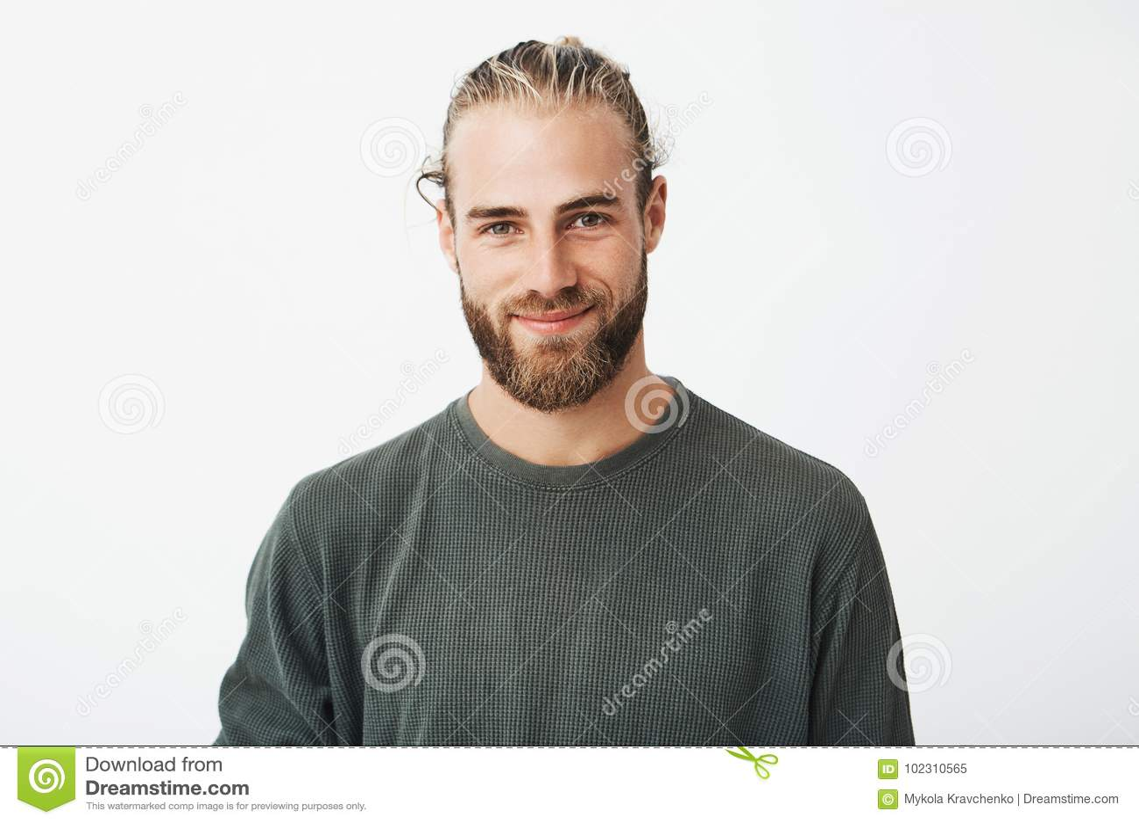 Retrato del individuo barbudo rubio maduro hermoso con el peinado de moda en camisa gris casual que sonríe y que mira in camera