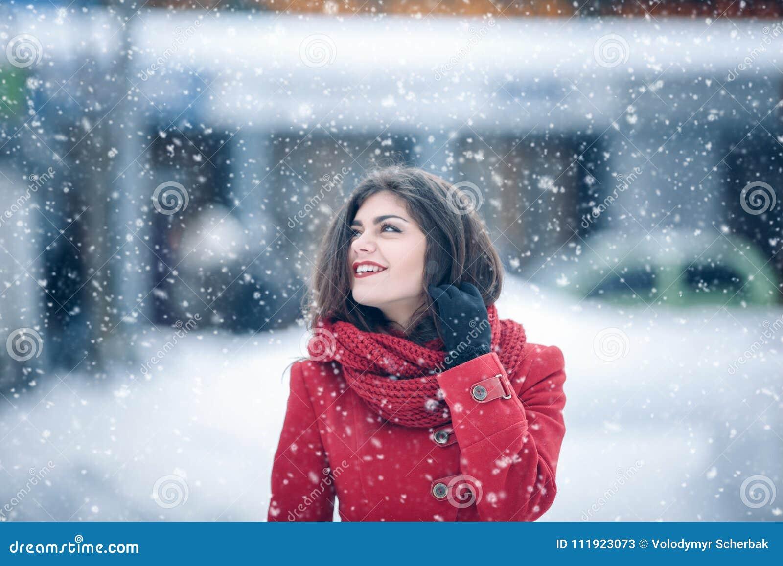 Retrato del invierno de la mujer morena hermosa joven que lleva la redecilla hecha punto y la capa roja cubiertas en nieve Fashio