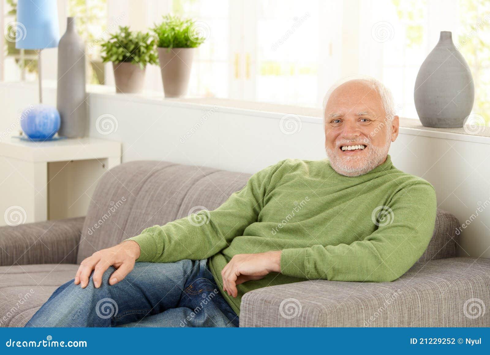Retrato del mayor feliz en el sofá