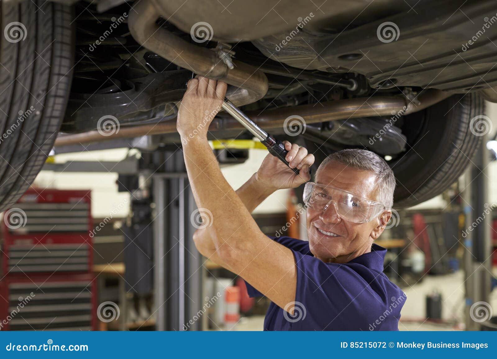 Retrato del mecánico de automóviles Working Underneath Car en garaje