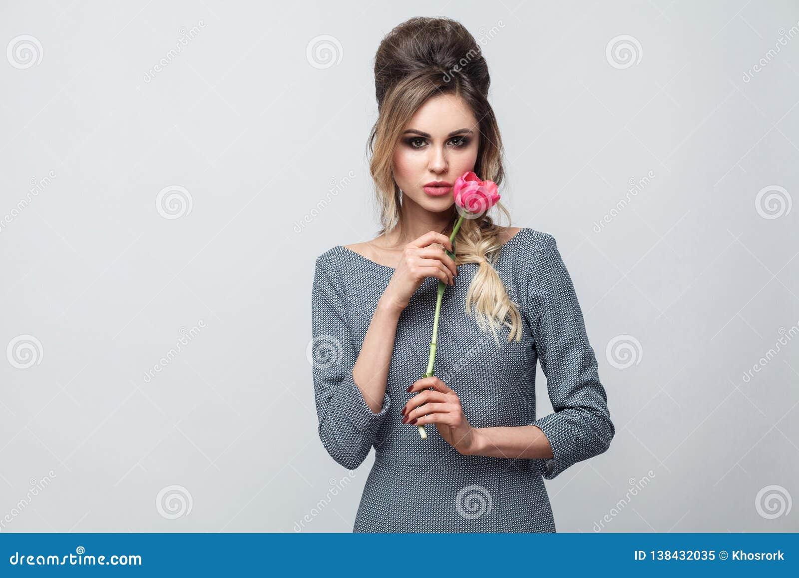 Retrato del modelo de moda atractivo hermoso en vestido gris con maquillaje y del peinado, colocándose, sosteniendo el tulipán ro