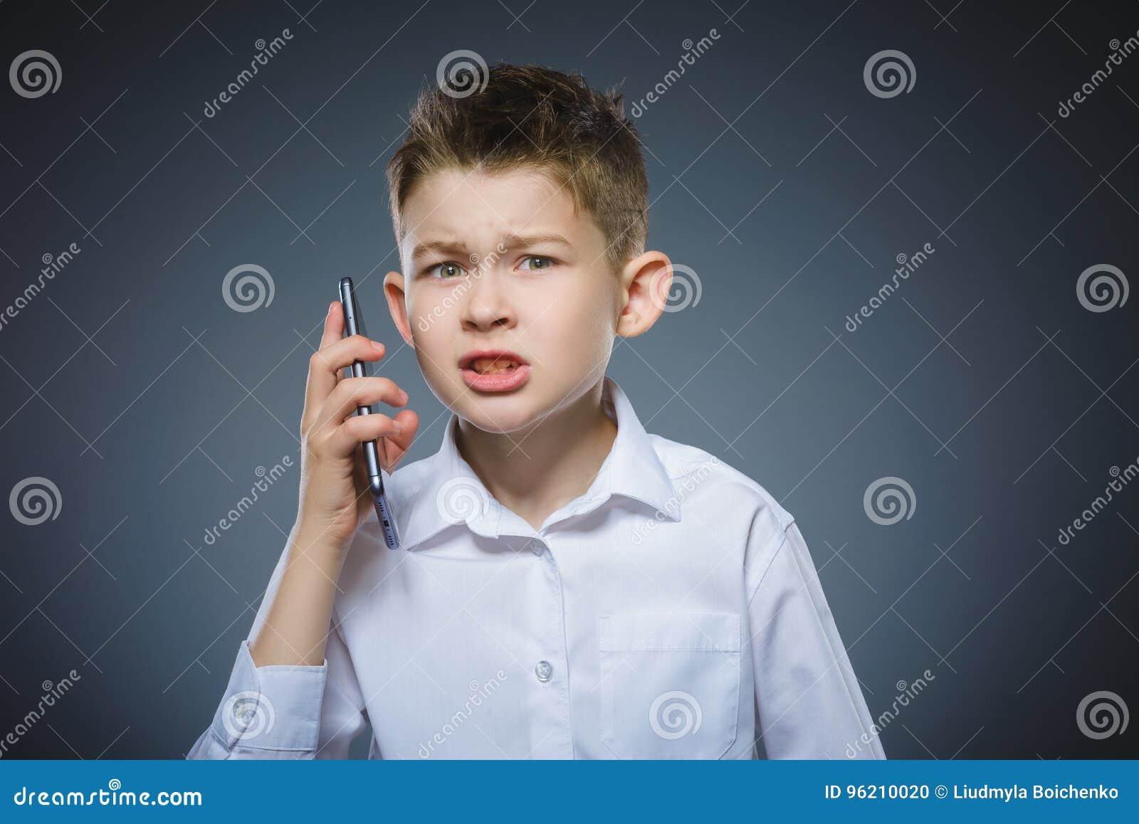 Retrato del muchacho de la ofensa con el móvil o el teléfono celular Emoción humana negativa