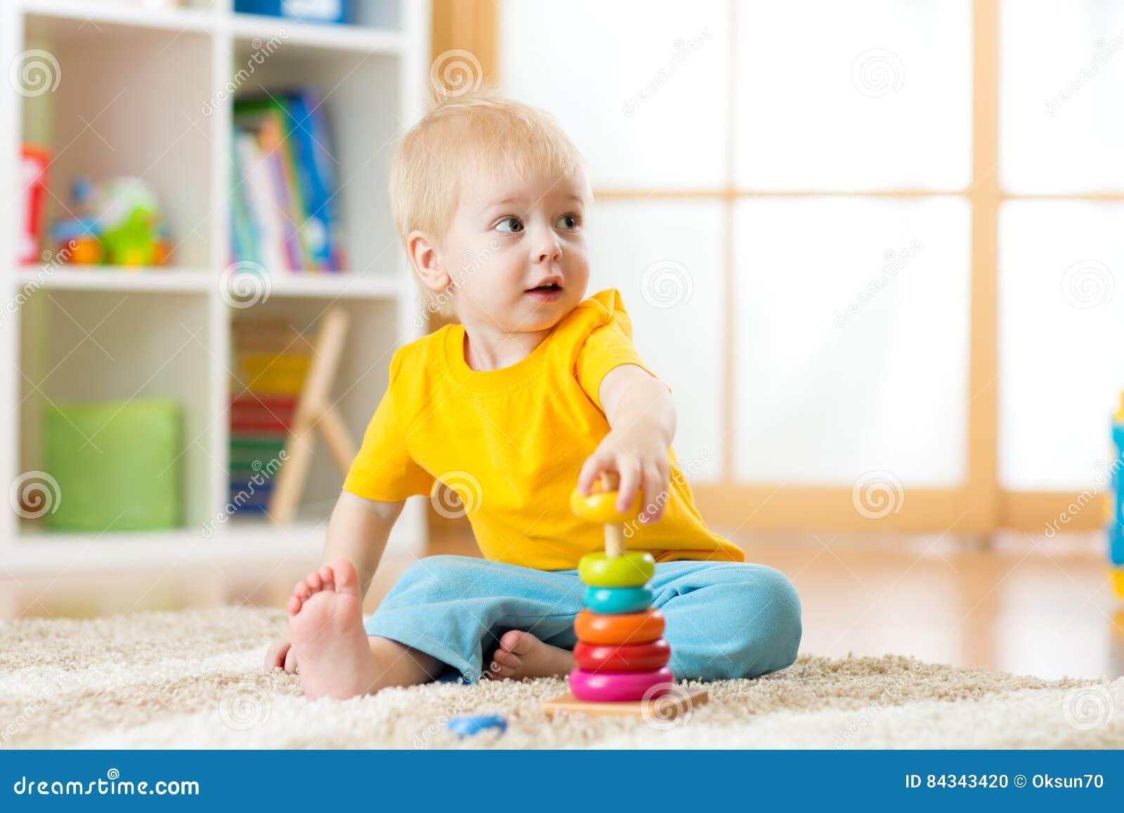 Retrato del muchacho lindo del niño que monta el juguete colorido de la pirámide en piso en la sala de estar