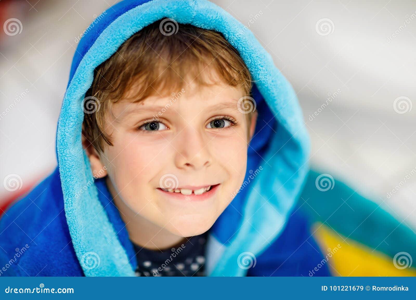 Retrato del muchacho sonriente hermoso del niño Niño feliz en albornoz azul