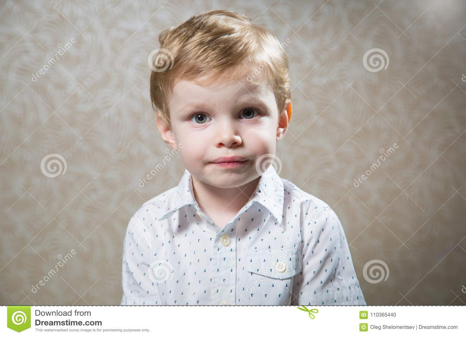 a941a60c8 El retrato del niño pequeño caucásico lindo weared la camisa blanca contra  la pared