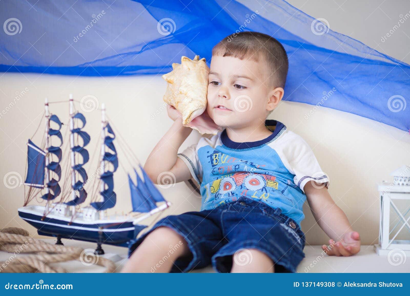Retrato del niño pequeño caucásico lindo y feliz que escucha cuidadosamente una concha de berberecho grande